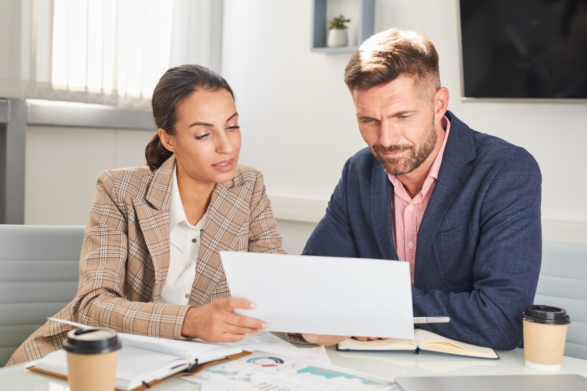 Portrait of two business people man and woman looking at documents during meeting in office