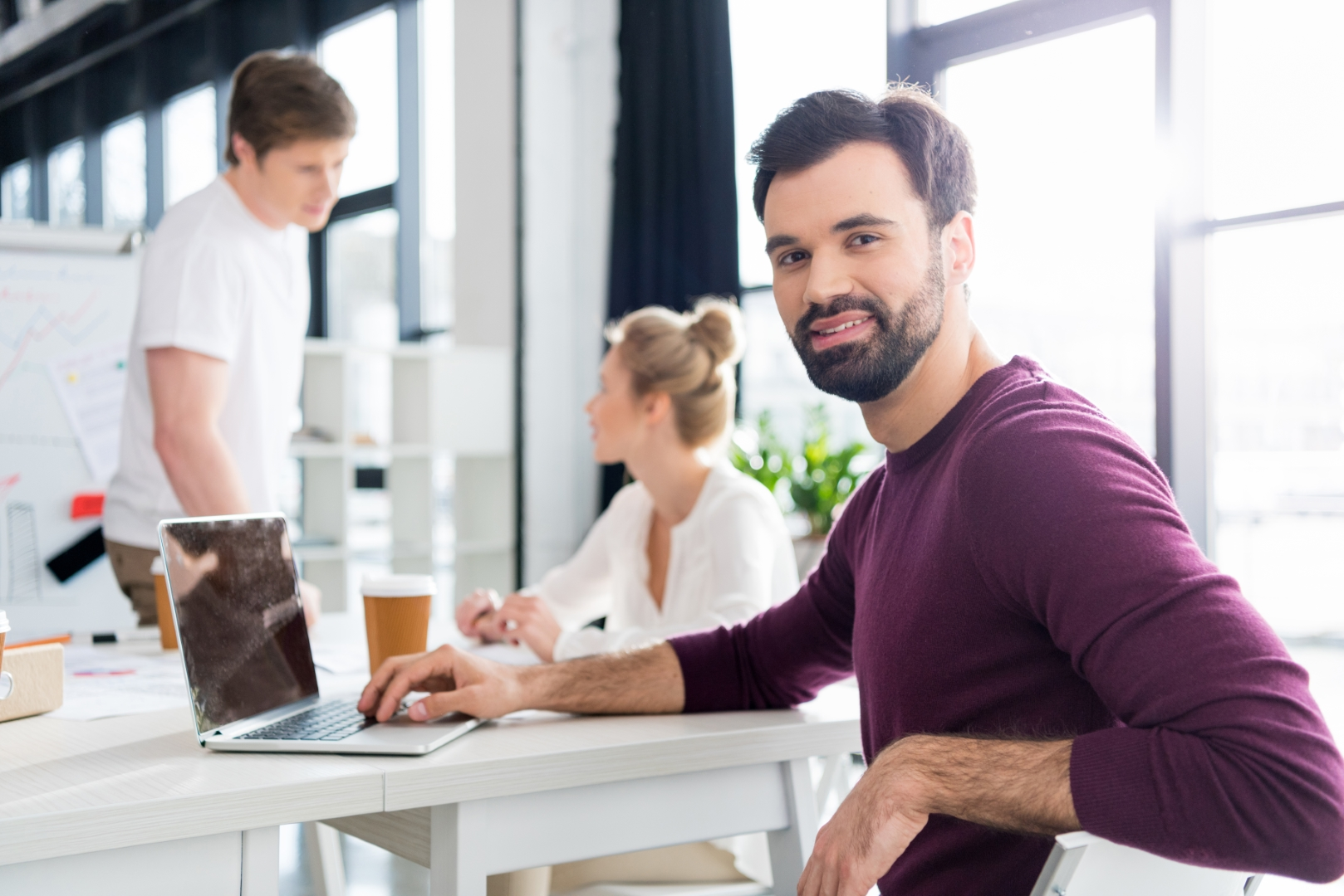 businessman working with laptop on workplace in office, colleagues behind, small business people