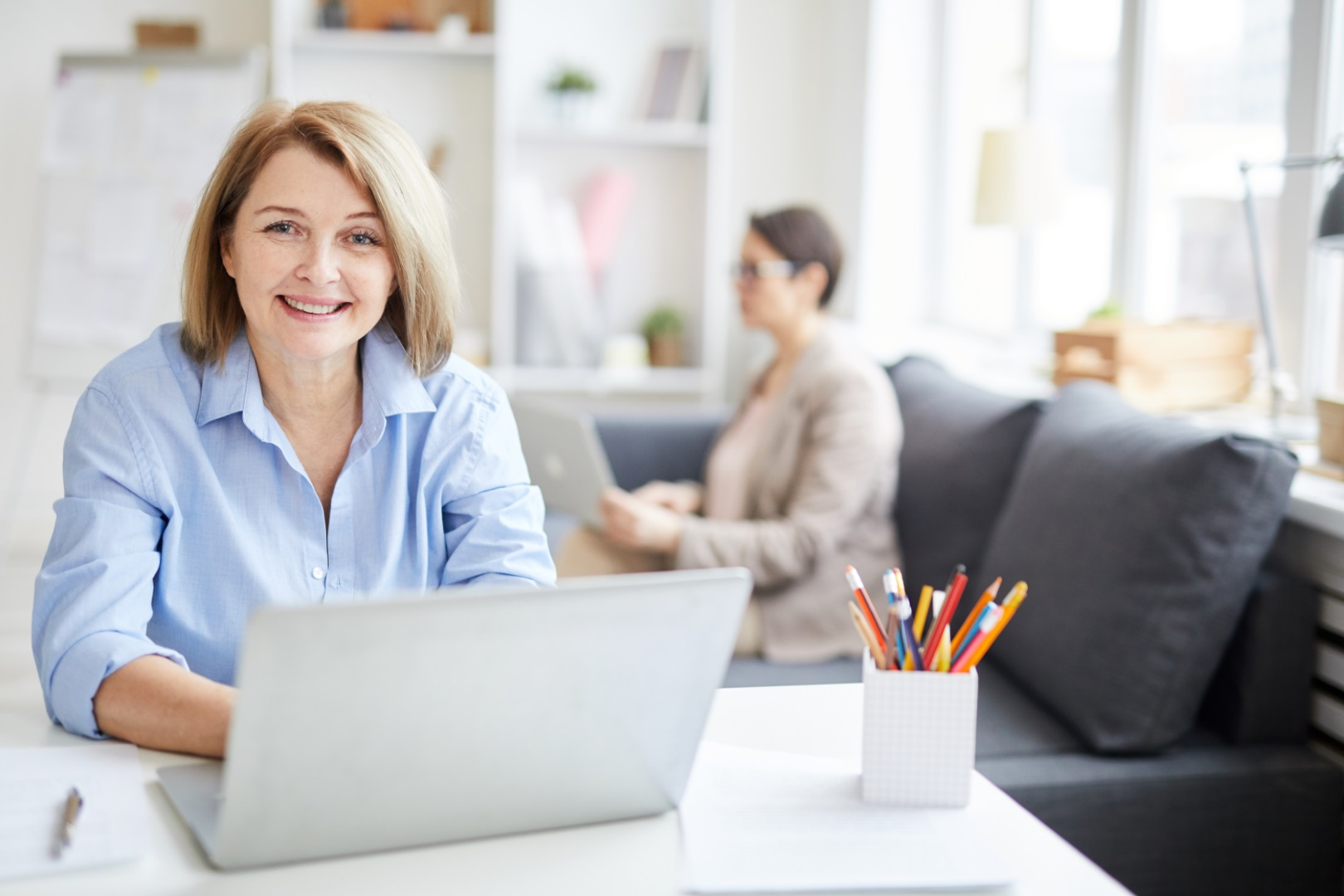 Portrait of successful businesswoman looking at camera and smiling while working in modern office, copy space