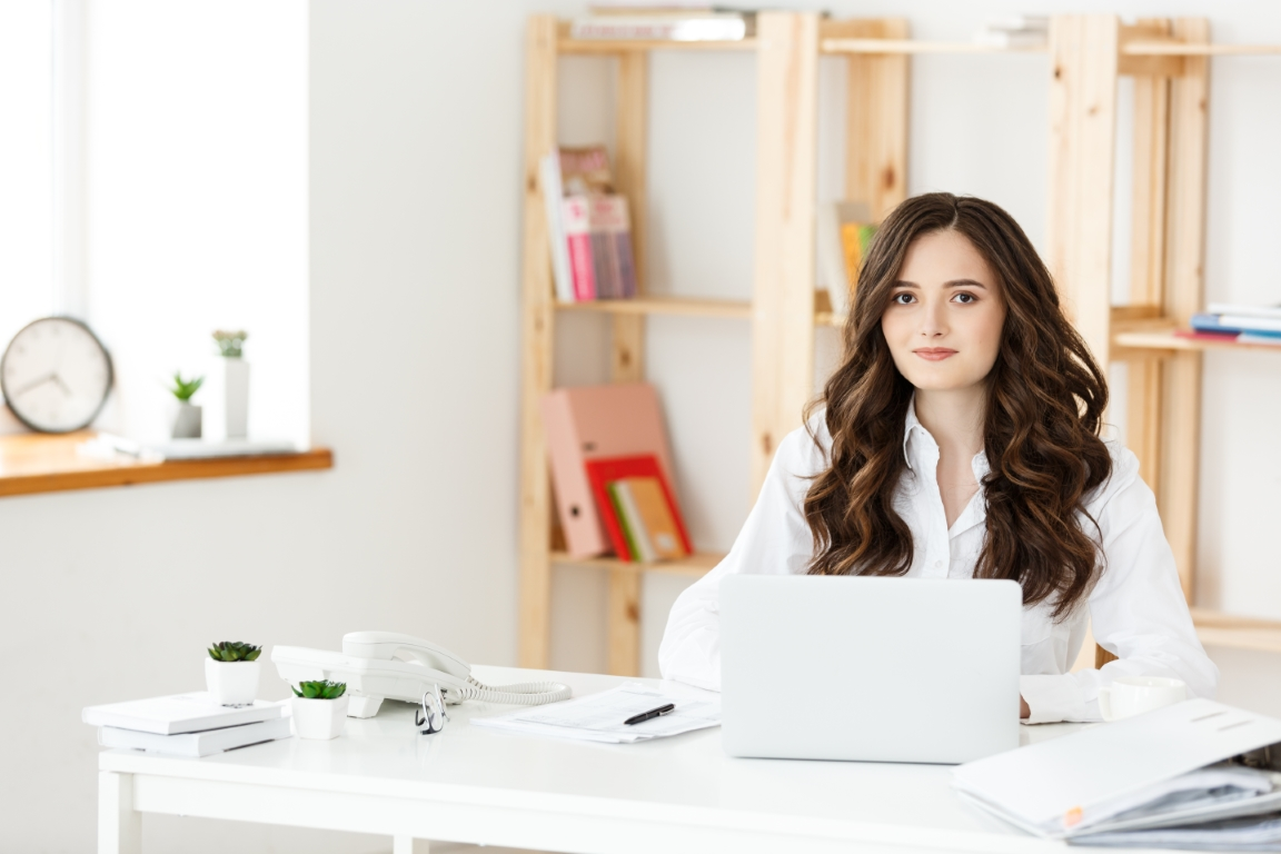 Young pretty business woman with notebook and document in the bright modern office indoors.